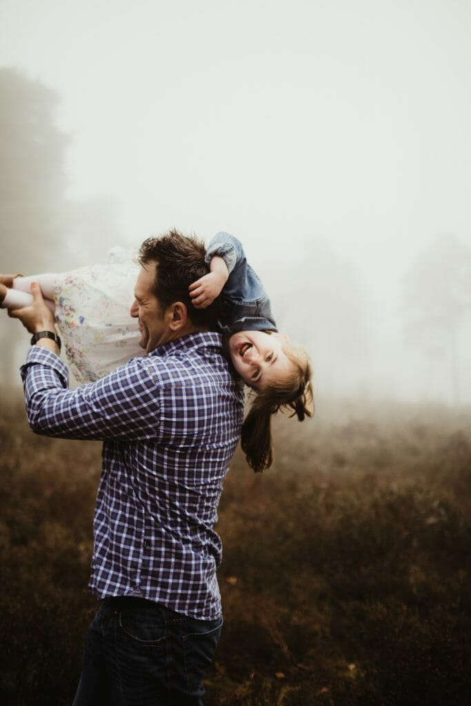 father and daughter playing in fog